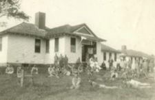 A group of men in front of a single-storied white building.