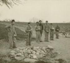 Seven young men and boys stand by a pile of rocks.