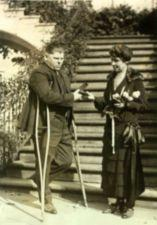 Mrs. Coolidge presents a medal to a man (L.B. Clark) on crutches.
