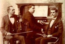 Portrait of three blind musicians seated with their instruments -- a violin, a clarinet, and a piano.