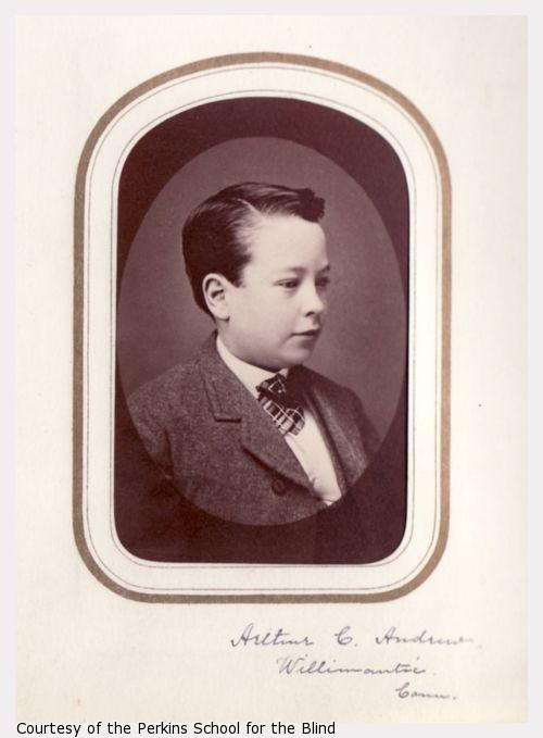 Portrait of Arthur C. Andrew, as a boy in three-quarter profile wearing a wool coat and plaid cravat.