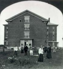 Stereo card showing male and female patients, including children, playing crocquet in front of a large brick building at Willard Asylum.
