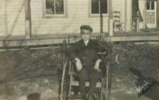 Photograph of a boy using a wheelchair in the yard of a small house.