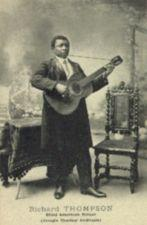 A black man wearing long coat and necktie stands playing a guitar in front of a table and a chair