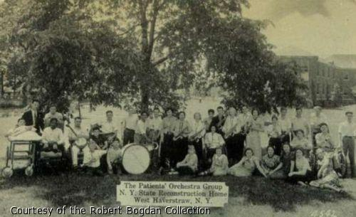 Photograph of large group of musicians posing with their instruments under a tree