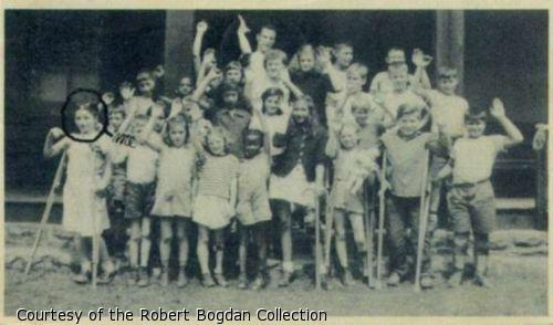 """Group photograph of campers waving.  One girl is circled in pen and labelled """"Me."""""""