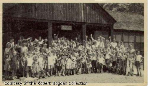 """Group photograph of campers waving.  One child is circled in pen and labelled """"Me."""""""
