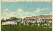 Colored postcard of staff and patients eating watermelon on lawn in front of low buildings with red and white awnings
