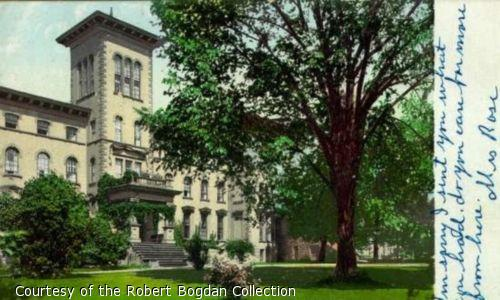 Color postcard of large building and lawn shaded by trees.