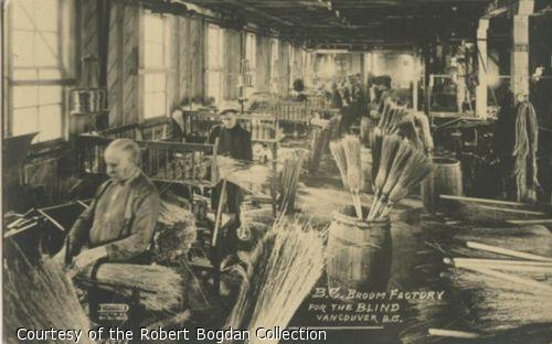 Men on benches making brooms by hand.