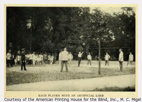 Group of amputees playing volleyball in a field.
