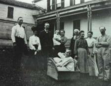 Photograph of a family posing outside of a house.  A young man wearing a night shirt sits in a wooden box.