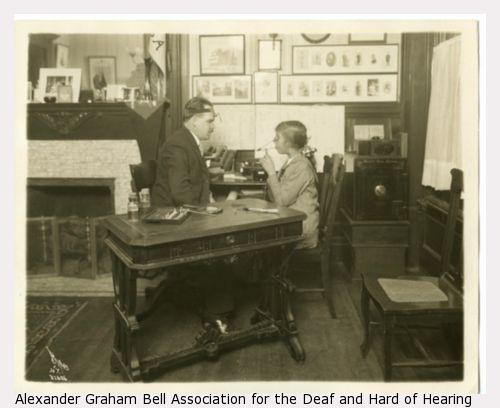 John Wright (left) examining a child at desk in an office.