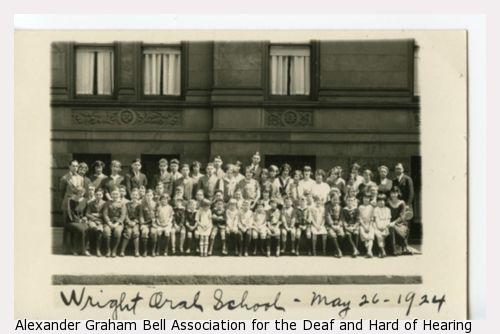 Group portrait of students and teachers posed outside the Wright Oral School.