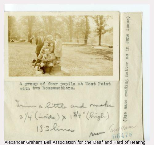 """Photograph of people on a grassy lawn with a description reading: """"A group of four pupils at West Point with two housemothers."""""""