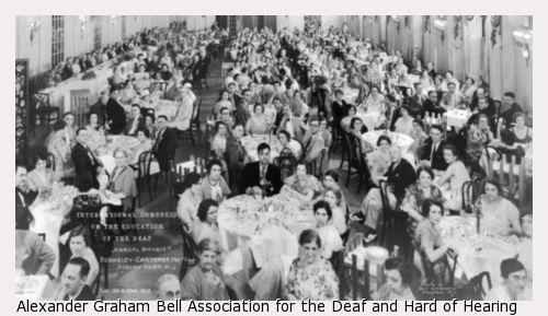 Group photograph of International Congress on the Education of the Deaf attendees sitting at large round tables in a banquet room.