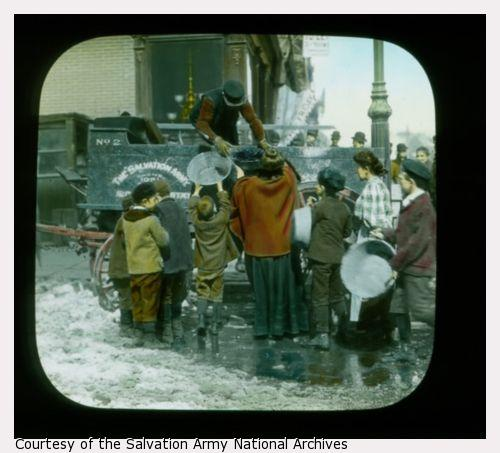 Lantern slide showing women and children with empty large pans. One woman is receiving a full pail of coal. Probably in NY