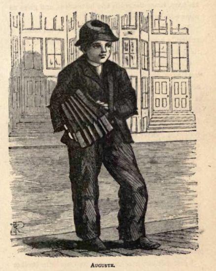 Boy holding an accordion on street.
