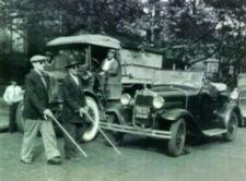 Photograph of two blind men, using white canes, crossing the street in front of a truck and a car.