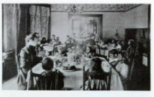 Young children of the McCowen School dine in a small parlor. Each table of children has a faculty member present.