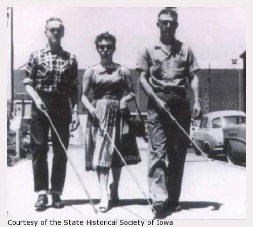 Three blind people walk down a city street, two men flanking a woman. Each carries a white cane in their right hand.