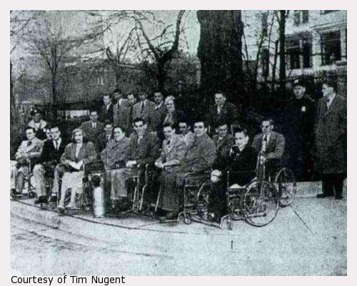 A newspaper photograph of about twenty people, about half of whom are in wheelchairs.