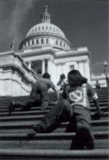 Two young people crawl up the steps of the Capitol Building.