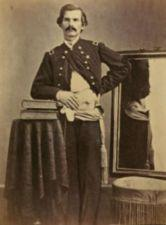 Henry Barnum in uniform.  His coat and shirt are pulled aside from his left hip revealing a wound through which a string passes.