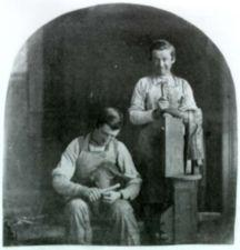 Two boys working as cobblers. One files the sole of a shoe. The other holds a hammer and last upright and smiles.