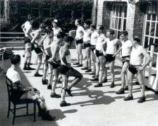 Two lines of men, most leg amputees, perform balancing exercises.