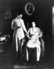 Woman in wheelchair having her pulse taken by nurse