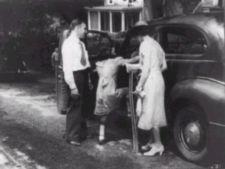 Little girl with braces on her legs climbs into car; man stands to her left and a woman, holding crutches, stands to her right