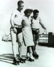Two veterans with prosthetic legs use a nurse for support as the three rollerskate.