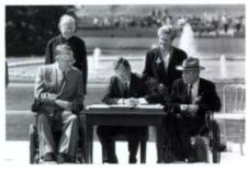 George Bush in front of White House sitting at table signing ADA; with a priest, a woman, and two men in wheel chairs