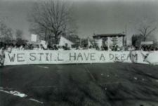 """Protestors march down the street carrying a large banner that reads """"We Still Have a Dream!"""""""