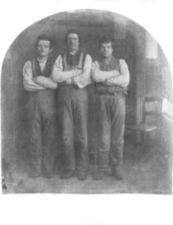 Three men stand with their arms folded across their chests.
