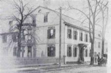Photograph of the Cogswell House, a large townhouse, with a horse drawn carriage on the street in front.