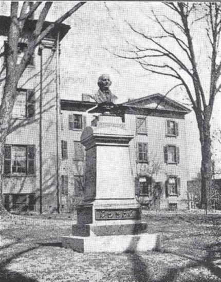 Bust of Laurent Clerc atop pedestal in front of large building