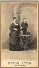 Major Atom, holding a top hat, stands on a table next to an average sized woman.