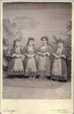 Four small-statured women standing.