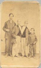 Chang and Eng stand between a young man and a boy.