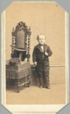 A short-statured young man in formal attire stands next to a chair.