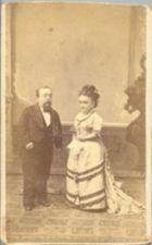 A short-statured man and woman, both formally dressed.