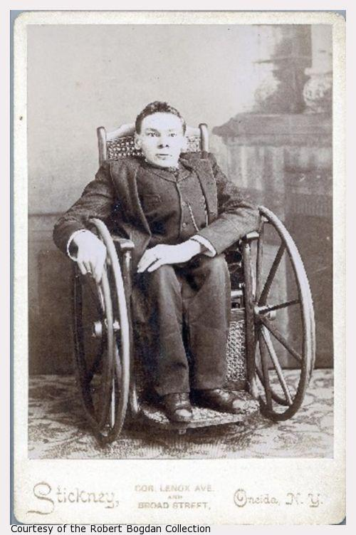 A young man in a wheelchair in a Victorian home.