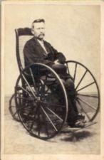 A man, with a hat on his lap, sits in a wheelchair.