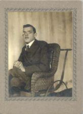 A young man with glasses sits in a wheelchair made of wicker.