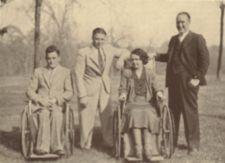 A man and and woman in wheelchairs with two men standing.