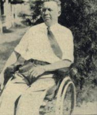 A middle-aged man sits in a wheelchair.