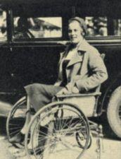 A woman sits in a wheelchair next to a car.